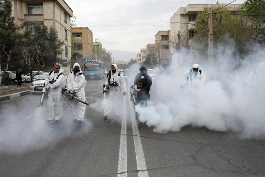 Firefighters wear protective face masks as they disinfect the streets in Tehran, Iran, on March 18, 2020.
