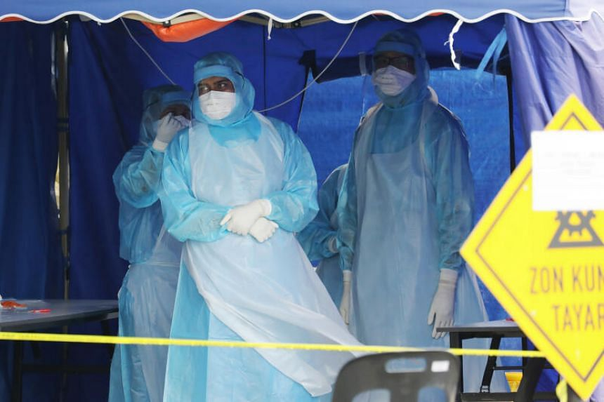 A photo taken on March 23, 2020 shows health workers in protective suits wait for patients in a tent erected to test for coronavirus at a clinic in Kuala Lumpur.