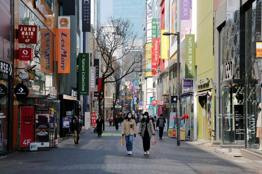 A photo taken on March 23, 2020 shows people with masks in a shopping district in Seoul.