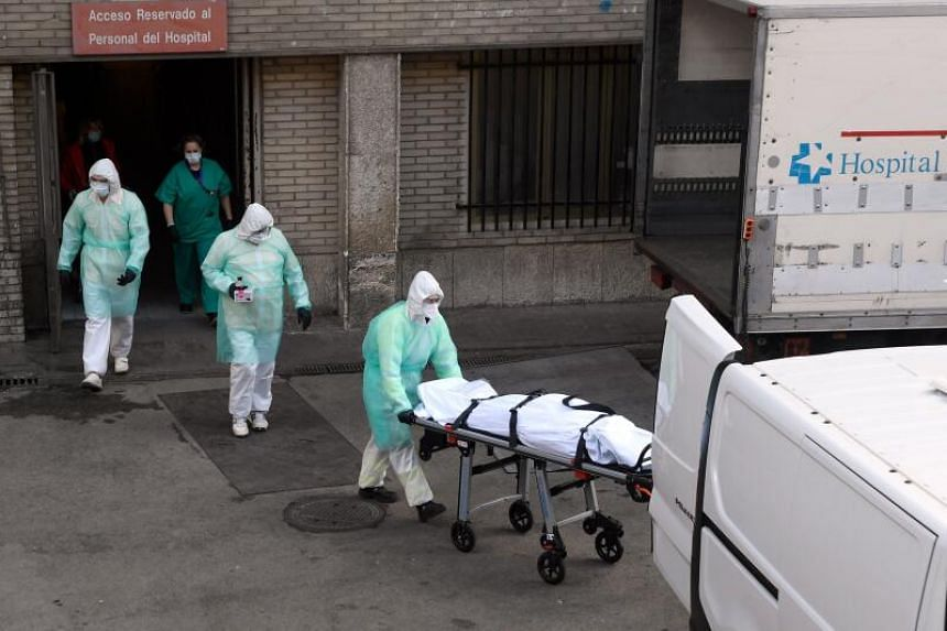 A health worker carries a body on a stretcher outside a hospital in Madrid, on March 25, 2020.