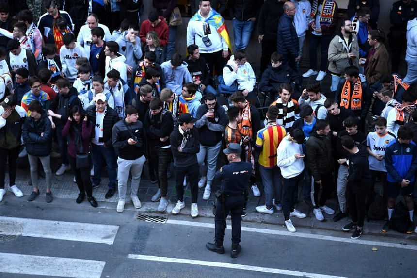 In a photo taken on March 10, 2020, fans gather outside Mestalla stadium in Valencia, Spain, before a match was played behind closed doors.