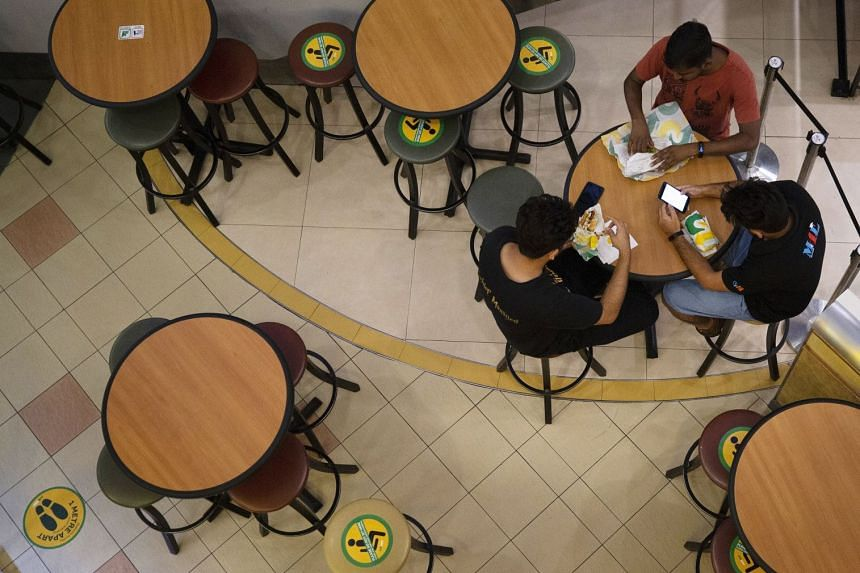 People sit at a restaurant at a shopping mall in Singapore where social distancing signs are seen on March 26, 2020.
