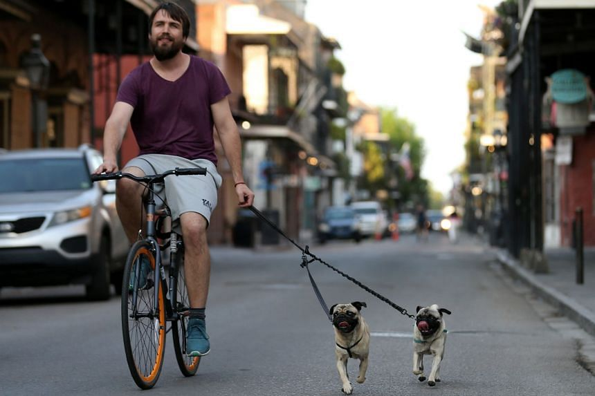 A man rides a bicycle while walking his dogs in the French Quarter of New Orleans, March 25, 2020.