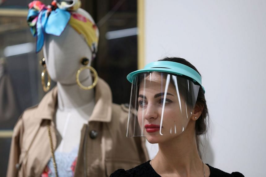 An employee wearing a protective mask stands near a mannequin at a department store in Moscow, Russia, March 26, 2020.