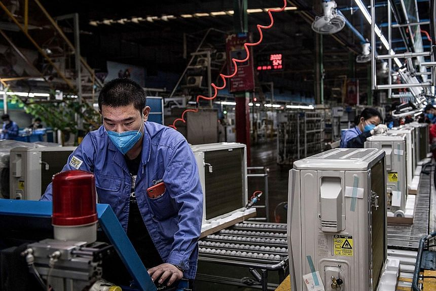 A worker at an air-conditioner production line at a Midea factory in Wuhan on Wednesday. Before the coronavirus outbreak, China's manufacturing sector was already suffering from the trade war with the US.