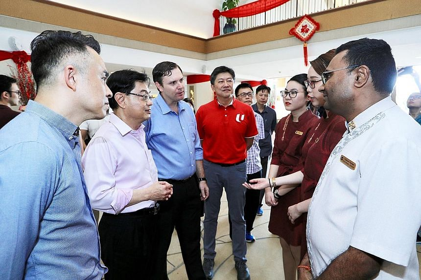 Left: Healthcare workers in the Singapore General Hospital isolation ward assisting in the transfer of a suspected Covid-19 patient to an isolation room. Singapore yesterday reported 52 new coronavirus cases. ST PHOTO: NEO XIAOBIN Above: Deputy Prime