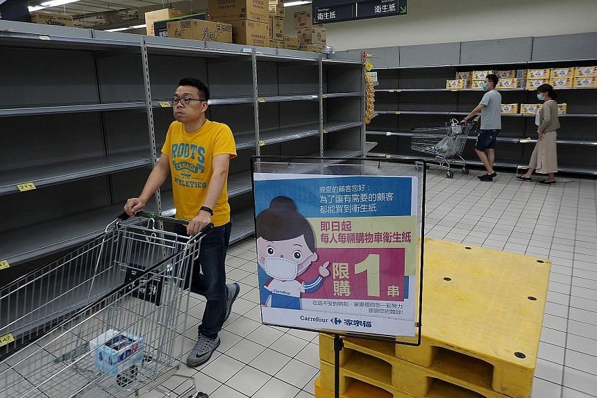 Empty shelves usually stacked with toilet paper at a Carrefour supermarket in New Taipei City last week. Panic buying of household staples such as toilet paper has occurred in nearly every country hit by the coronavirus. Sacks of rice at a National F