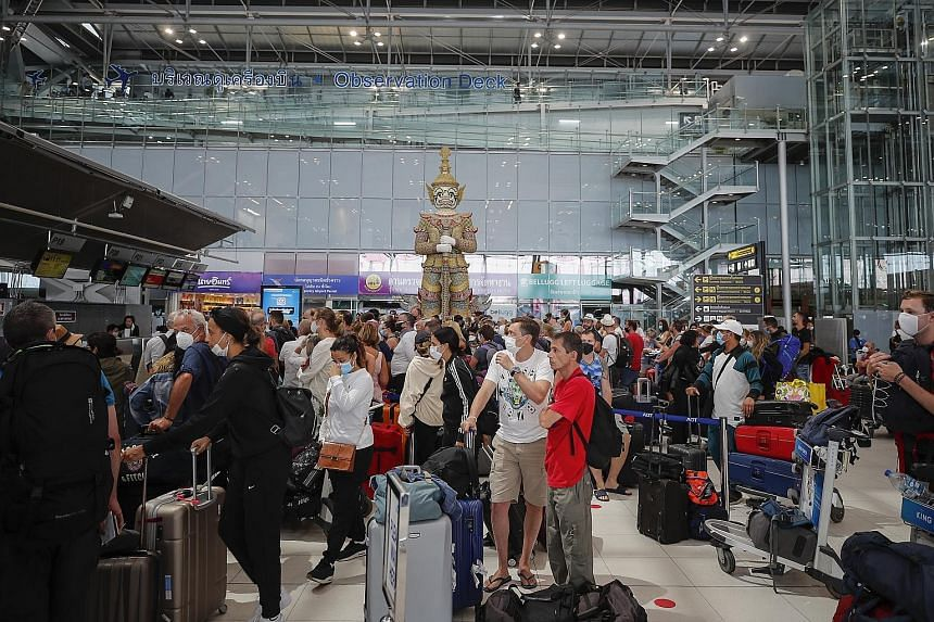 Travellers at the check-in counter of Suvarnabhumi international airport in Bangkok on Wednesday. Thailand has banned the entry of foreigners, with the exception of those residing and working in the country as well as diplomats, as part of the govern