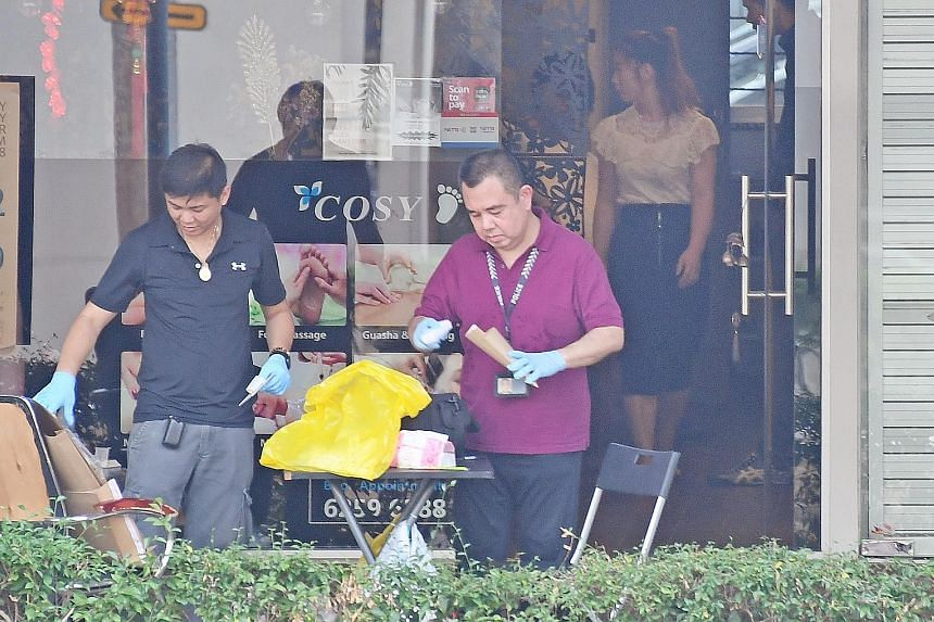 """Police personnel collecting evidence from Cozy Spa at Block 532 Ang Mo Kio Avenue 5, where Danon Tay Kok Lee threatened three women with a penknife and Yeo Shuxing removed the spa's closed-circuit television camera. They were there to look for the """"b"""