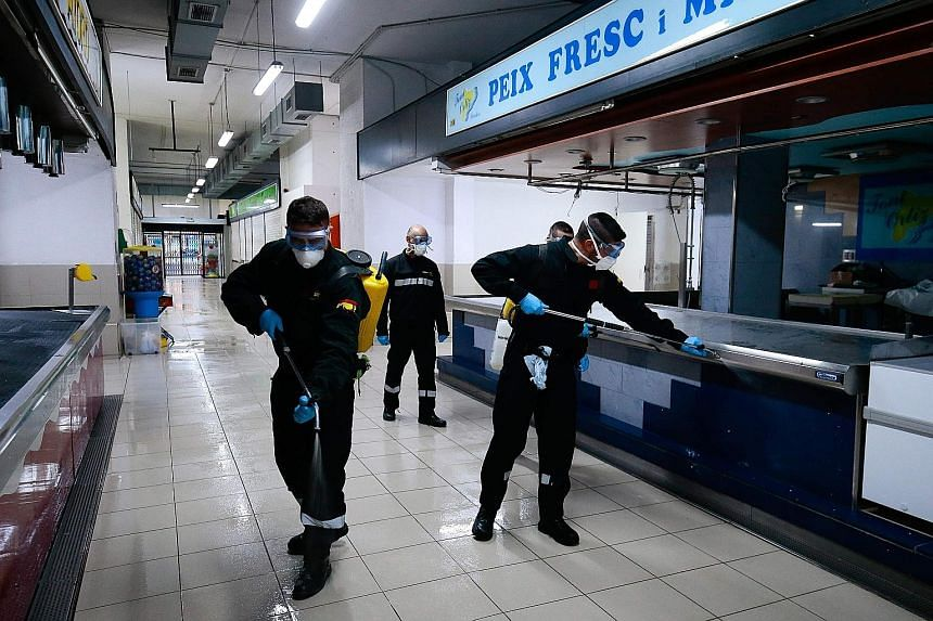 Members of Spain's Military Emergencies Unit carrying out general disinfection at a local market in Badalona, near Barcelona, on Wednesday. PHOTO: AGENCE FRANCE-PRESSE