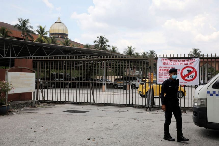 A police officer wearing protective mask stands guard outside the Seri Petaling Mosque, in Kuala Lumpur, Malaysia, on March 18, 2020.
