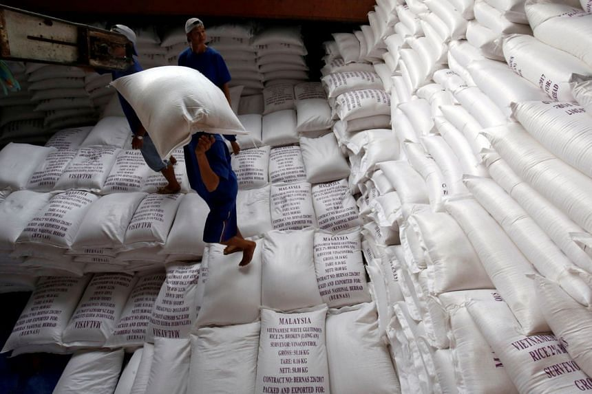 In a photo taken on July 6, 2017, men load rice bags to a ship for export at a rice processing factory in Vietnam's southern Mekong delta.
