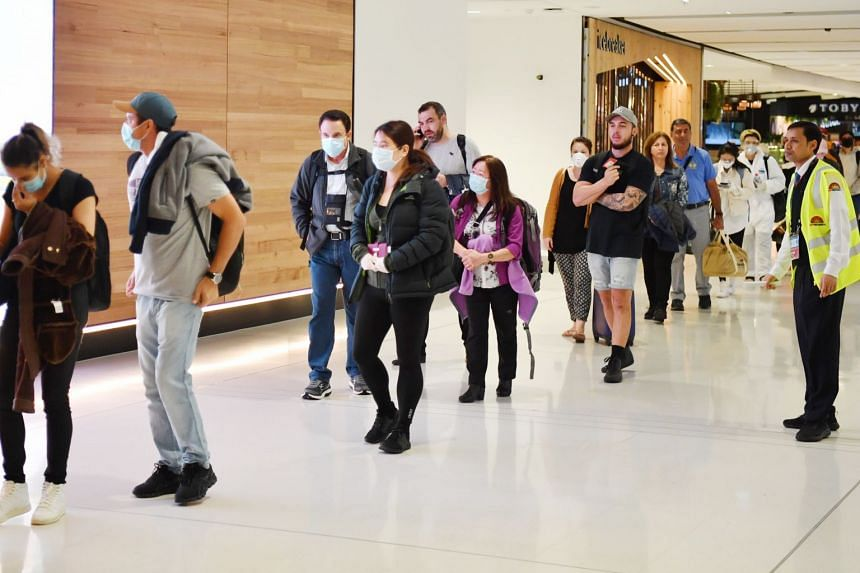 Travellers wearing masks arrive at Sydney International Airport, Sydney, Australia, on March 27, 2020.