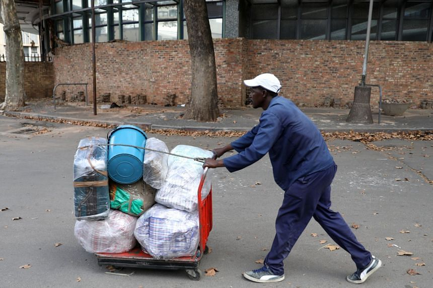 A man pushes a trolley loaded with his luggage at Park Station, which connects all provinces in the country, ahead of a nationwide lockdown for 21 days to try to contain the coronavirus outbreak, in Johannesburg, South Africa, on March 26, 2020.