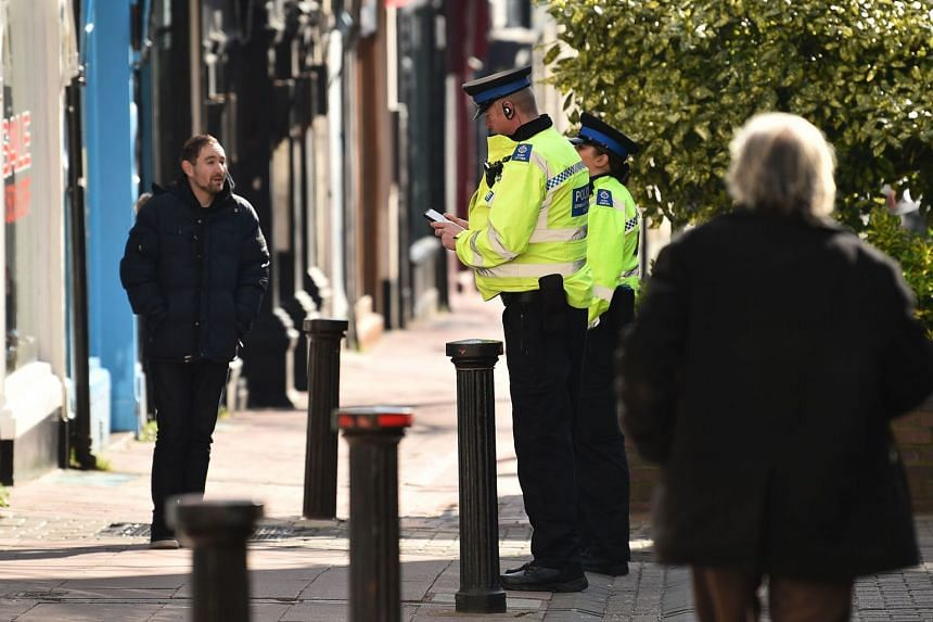 Police community support officers talk to a man on a street in Brighton, southern England, after the British government ordered a lockdown.