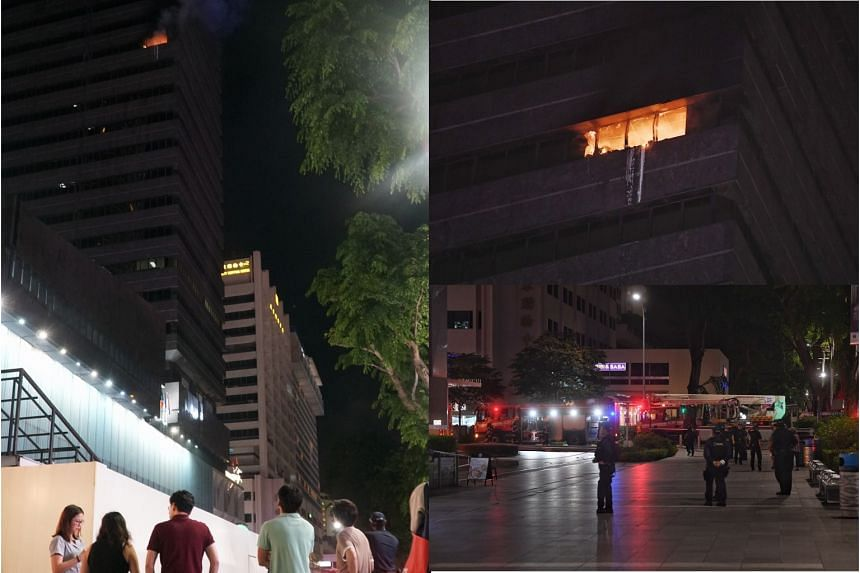 A fire (top right) broke out at Liat Towers (left) in Orchard Road on Wednesday evening. Police personnel and Singapore Civil Defence Force firefighters arrived at the scene (bottom left) after receiving an alert at about 10pm.