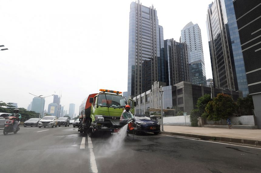 A worker sprays disinfectant on a street in Jakarta on March 27, 2020. Indonesia reported 153 new cases on March 27, the highest single-day jump.