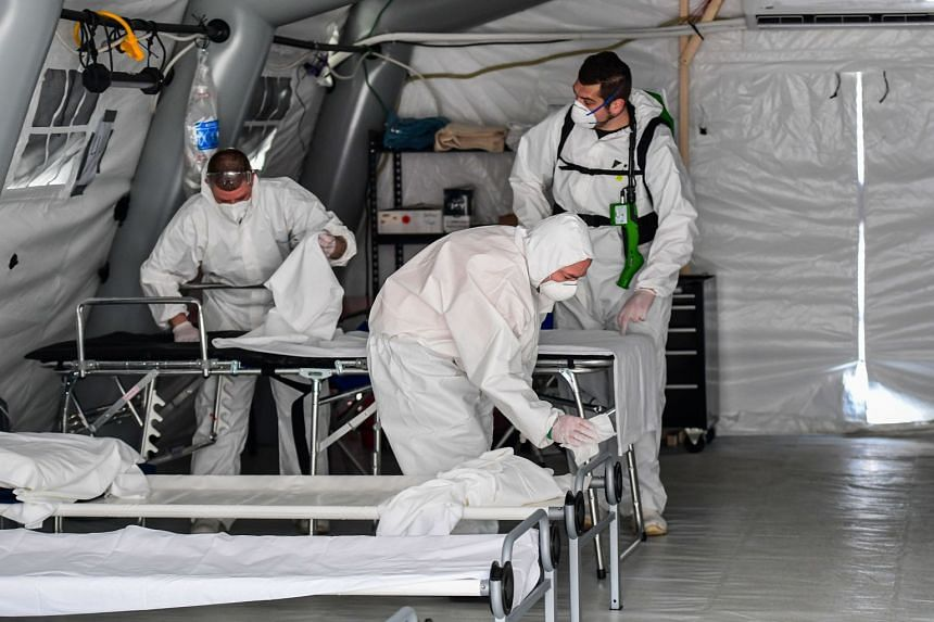 Cleaning personnel in protective gear disinfect patients' beds at a field hospital for coronavirus patients in Cremona, Italy.