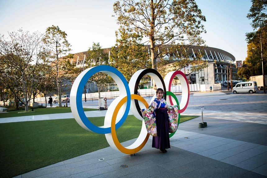 A woman wearing a traditional Japanese kimono poses next to the Olympic rings in front of the Japan National Stadium, the main venue for the Tokyo 2020 Olympic Games, in Tokyo, on March 25, 2020.