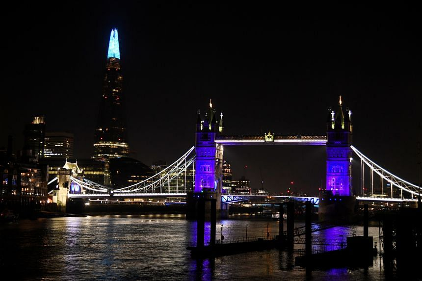 Tower Bridge and the Shard are lit blue in support of the NHS, as the spread of the coronavirus disease (COVID-19) continues, in London, Britain, on March 26, 2020.