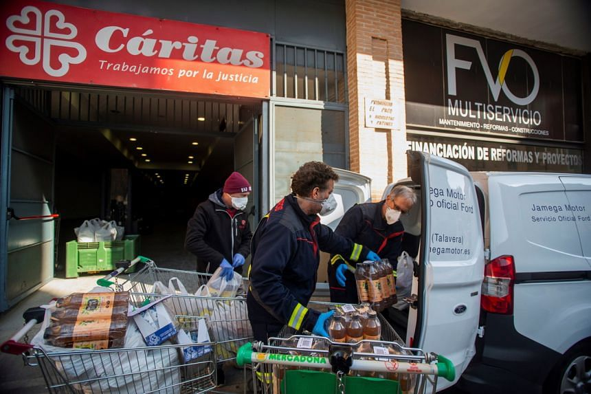 Firemen deliver emergency food bags to the home of elderly and dependent people in Talavera de la Reina, Toledo, Spain, on March 25, 2020.