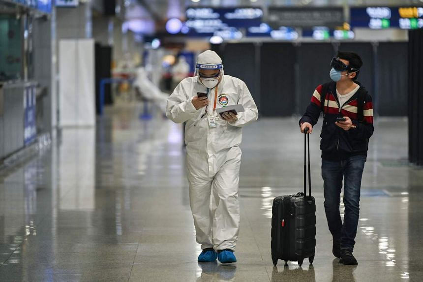 A member of the airport security walks with a passenger upon his arrival at Shanghai Pudong International Airport in Shanghai, on March 26, 2020.
