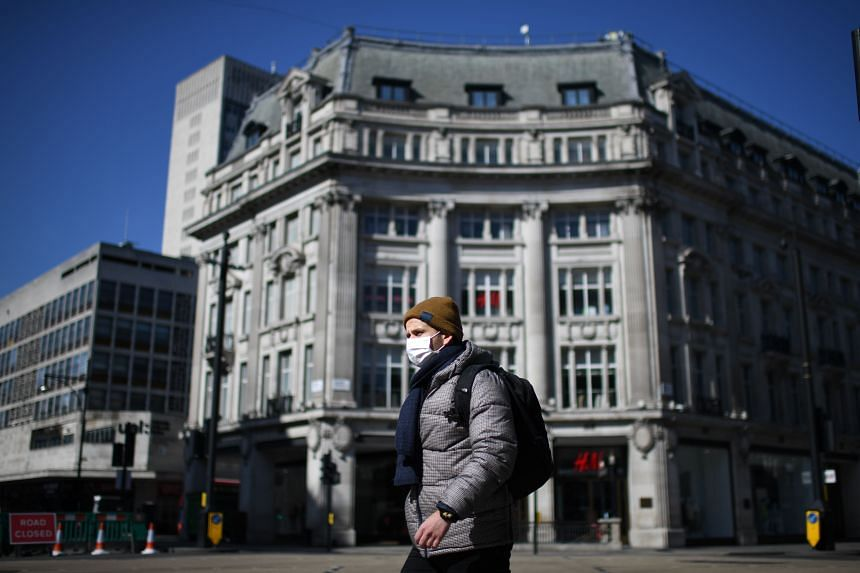 A pedestrian wearing a mask walks at Oxford Circus in central London on March 24, 2020, after Britain ordered a lockdown to slow the spread of the novel coronavirus.