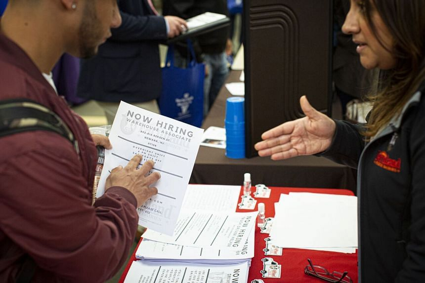 In a photo taken on Nov 8, 2019, a Farmland employee offers information to attendees during a Port Authority of New York and New Jersey job fair at the Union County College in Elizabeth, New Jersey.