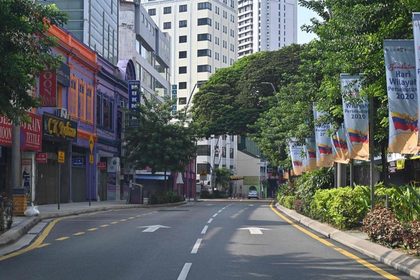 A motorist travels on the near-deserted a road during the control of movement in Kuala Lumpur, Malaysia, on March 22, 2020.
