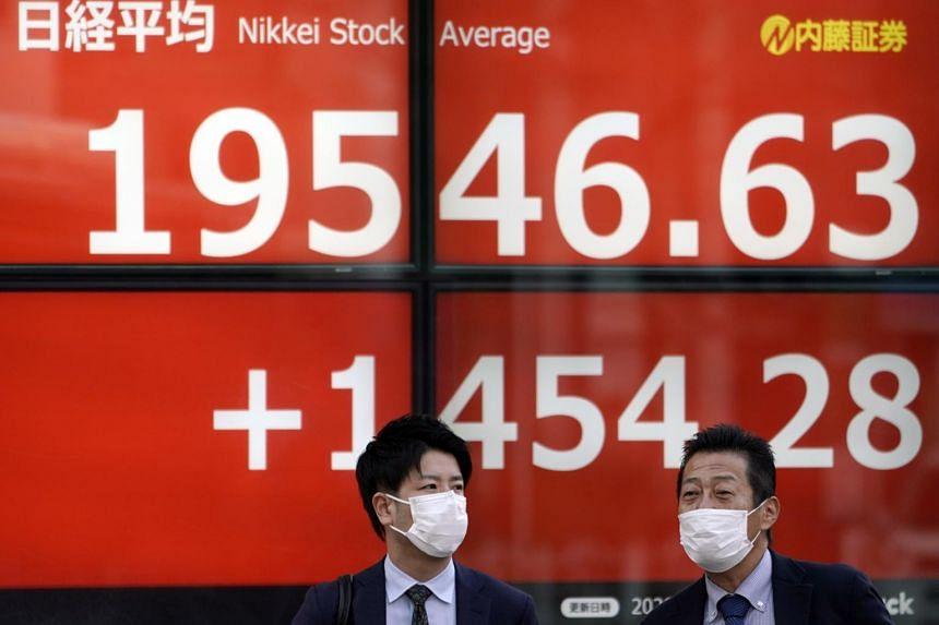 Pedestrians wearing masks walk before a stock market indicator board in Tokyo, Japan, on March 25, 2020.