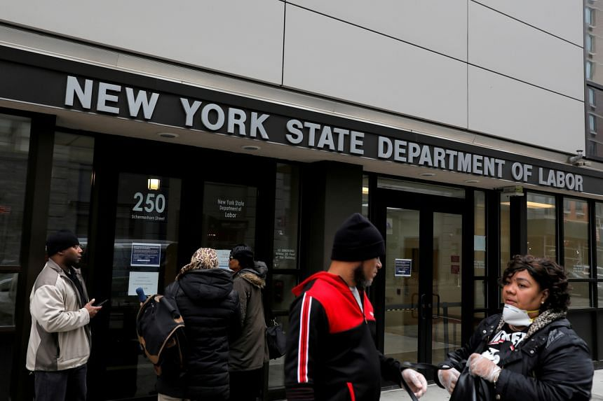 People gather at the entrance of the New York State Department of Labor offices, which closed to the public due to the coronavirus outbreak, on March 20, 2020.