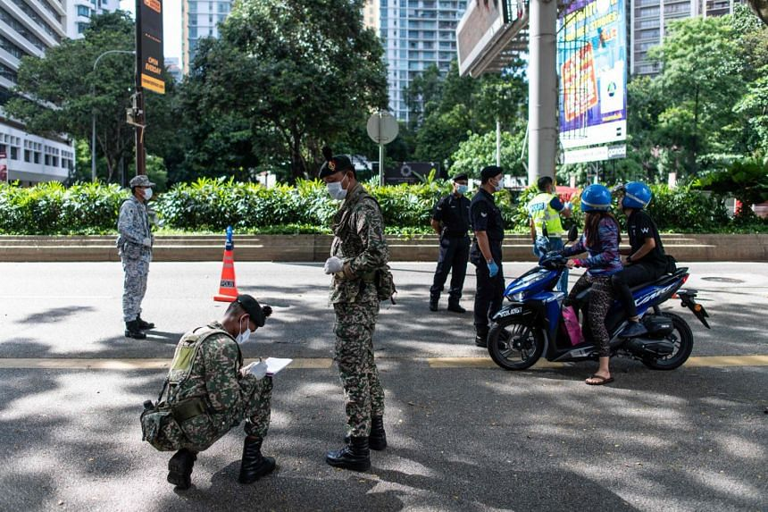 Members of the Royal Malaysia Police and soldiers stop motorists at a roadblock set up to maintain the Movement Control Order in Kuala Lumpur, Malaysia, on March 25, 2020.