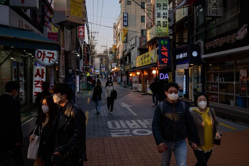 People wearing face masks walk through an alleyway in Seoul, South Korea, on March 24, 2020.