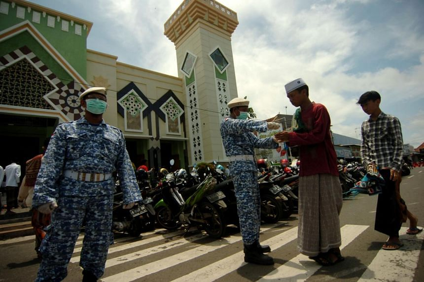 A worker applies hand sanitiser to the people before Friday prayers at a mosque, in Tegal, Central Java province, Indonesia, on March 20, 2020.