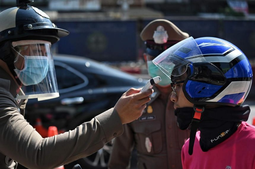 A member of the Royal Thai Police takes a food delivery rider's temperature at a checkpoint on the outskirts of Bangkok, on March 26, 2020.