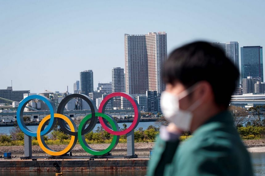 A man wearing a protective face mask stands before the Olympic rings in Tokyo's Odaiba district.