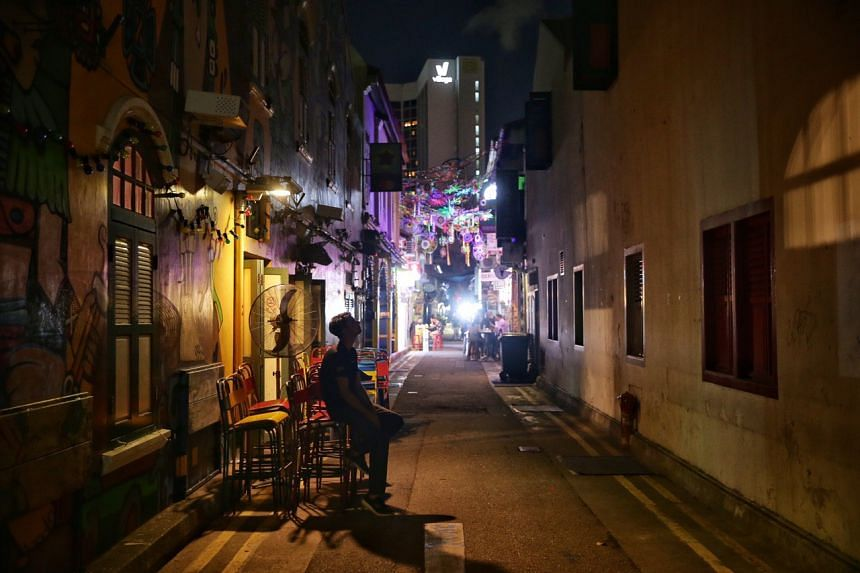 A staff (from India, New Delhi) of Piedra Negra (a bar and restaurant) pondering his future outside the bar at 11.34pm along Haji Lane, as they began to close from 11.30pm, ahead of the stipulated 11.59pm, on March 26, 2020.