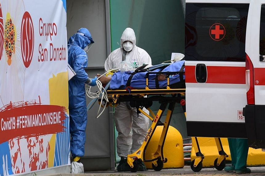 Medical workers stretcher a patient from an Italian Red Cross ambulance into an intensive care unit set up in a sports centre outside the San Raffaele hospital in Milan.