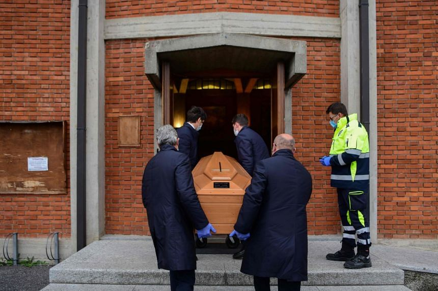 Pallbearers bring the coffin of deceased person to be stored into the church of San Giuseppe in Seriate, near Bergamo, Lombardy, on March 26, 2020.