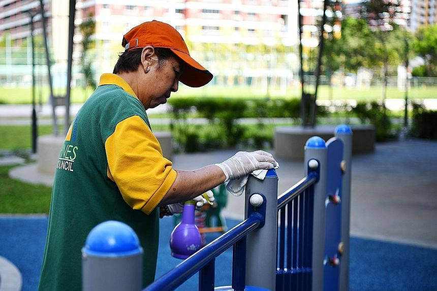 Cleaner Ling Li, 70, cleaning a playground in Tampines last month. Disinfectants and alcohol-based sanitiser break the lipid membrane encasing a coronavirus' genetic material, rendering the virus impotent and incapable of infecting its host.