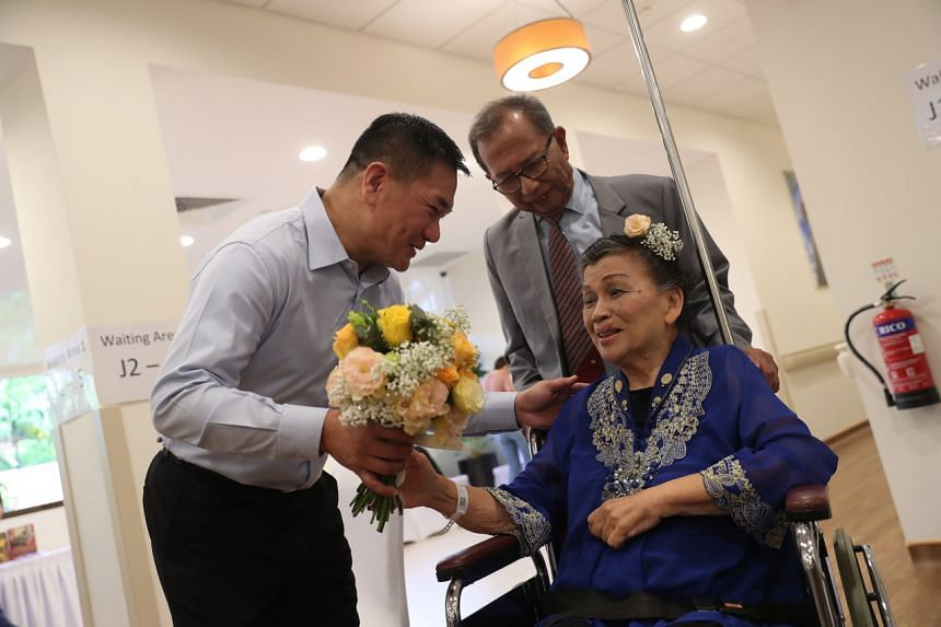 Mr Teo Choo Chuan (left), the son of Madam Liong May Swan, presenting a bouquet to her before her marriage to Mr Tom Iljas (centre), on March 28, 2020.