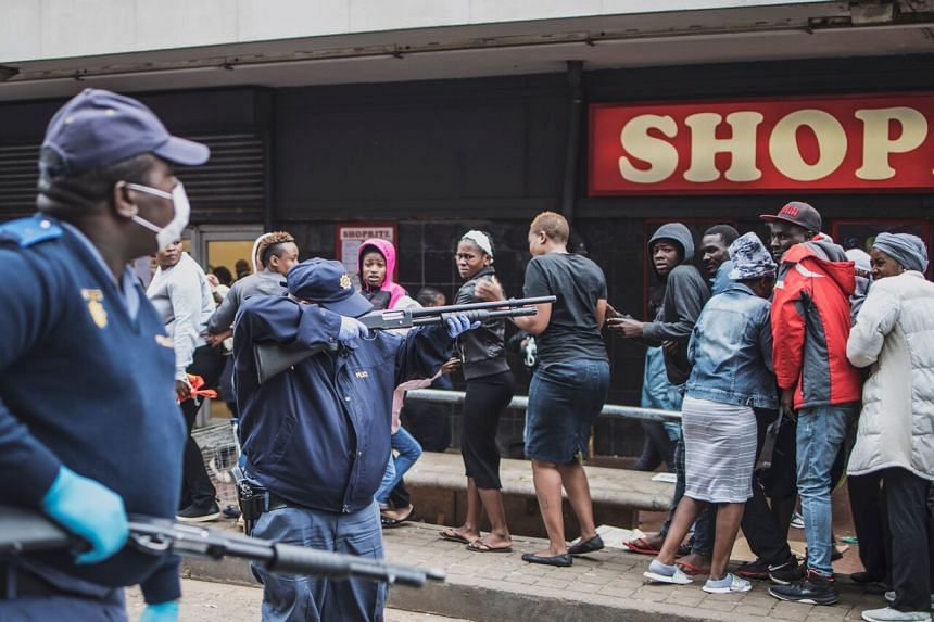 A South African police officer forcing people to disperse and observe the safety distance as they queue outside a supermarket in Yeoville, Johannesburg, on March 28, 2020.
