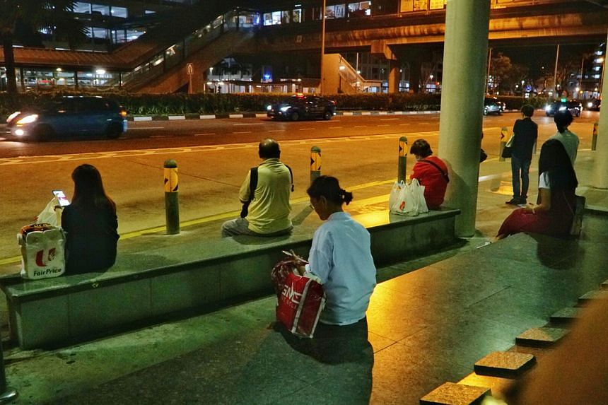 Commuters at the bus stop outside Admiralty MRT station on March 27, 2020.