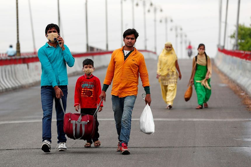 Sushil Kumar, a migrant worker, walking along a highway with his family to return to their village in Gajraula, India, on March 27, 2020.
