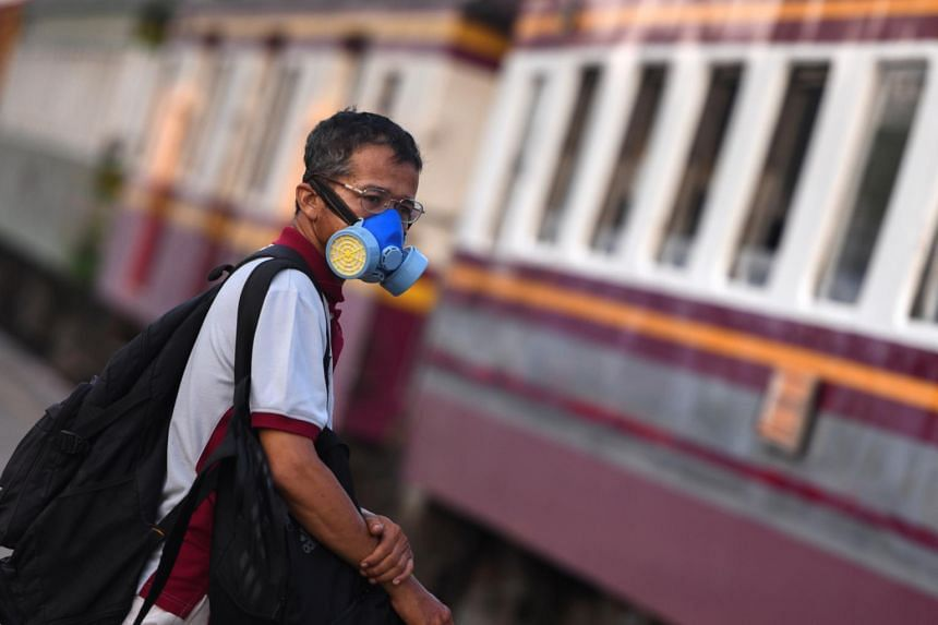 A man wearing a protective face mask is seen at a train station in Bangkok on March 27, 2020.
