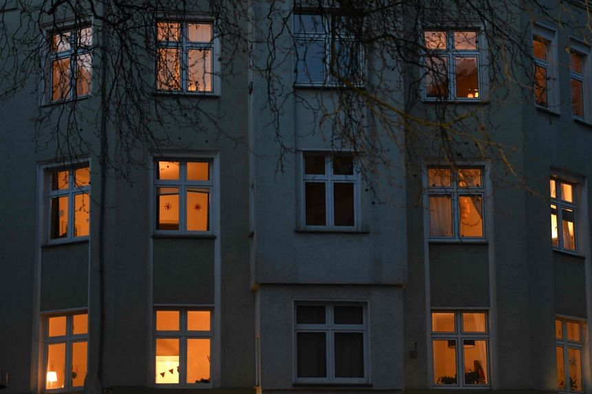 A picture taken on March 22, 2020, shows the facade of a building with illuminated flats in Dortmund, western Germany.
