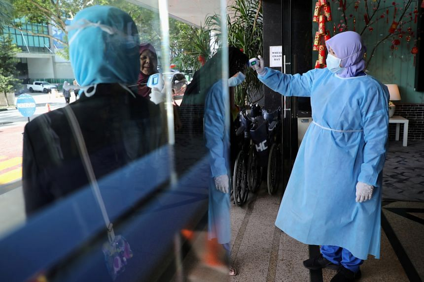A nurse checks the temperature of a visitor as part of the coronavirus screening procedure at a hospital in Kuala Lumpur, Malaysia, on Feb 3, 2020.