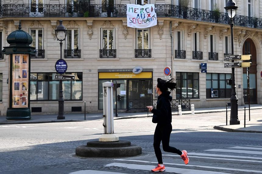 A jogger runs in the street near a sign hanging from a balcony thanking medical workers, in Paris, on March 27, 2020.