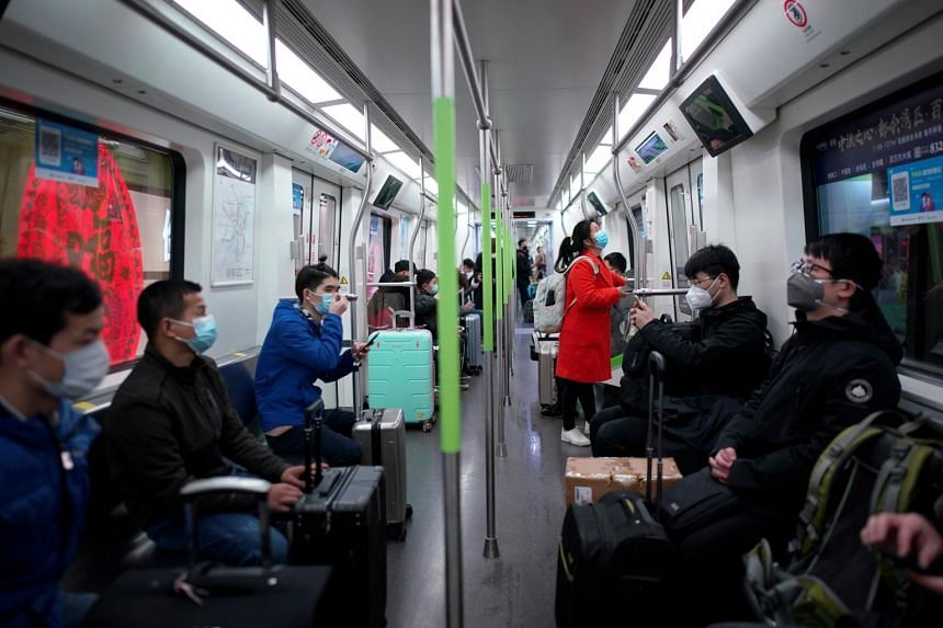 Passengers wearing face masks ride a subway train on the first day the city's subway services resumed in Wuhan on March 28, 2020.