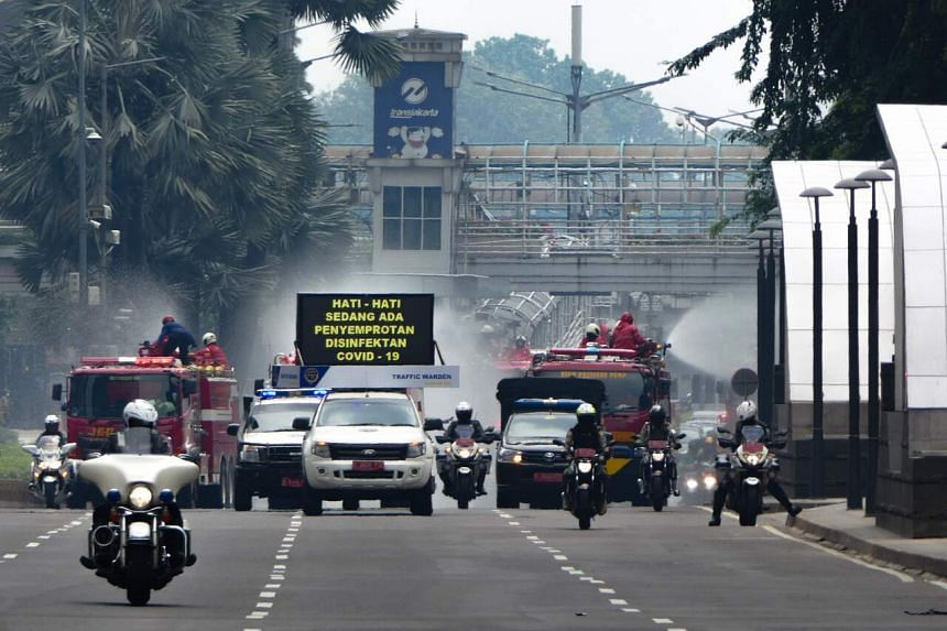 Firefighters spray disinfectant on a road in downtown Jakarta on March 28, 2020.